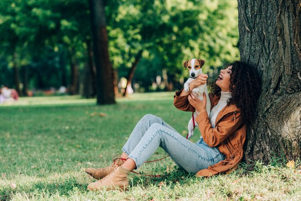 woman relaxing in the park with her dog